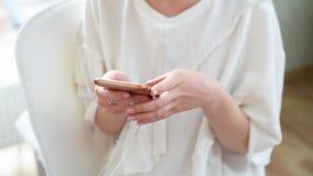 Kobiety r?ka pisa? na maszynie mobiln? wiadomo?? na parawanowym smartphone Zako?czenie w g?r? kobiety wr?cza mienia smartphone i  zbiory