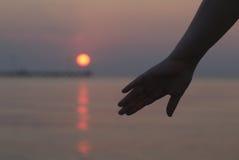 Kobiety ręka sylwetkowa przeciw zmierzchowi Zdjęcie Stock