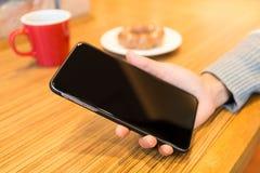 Kobiety ręka trzyma pustego ekran telefon komórkowy Zdjęcie Stock