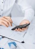 Kobiety ręka z kalkulatorem i papierami Obraz Royalty Free