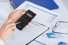 Kobiety ręka z kalkulatorem i papierami Obrazy Stock