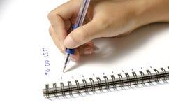 Kobiety ręki writing z piórem na notatniku Obraz Stock