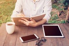 Kobiety ręki writing notatnik i telefon, pastylka na stole w ogródzie Zdjęcie Stock