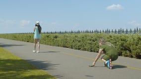 Kobiety rolkowy podnosić w górę portfla od parkowej alei zdjęcie wideo