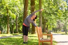 Kobiety rozciąganie w parku na słonecznym dniu zdjęcia stock