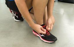 Kobiety są ubranym buty przygotowywających dla ciężaru traning przy gym Obraz Royalty Free