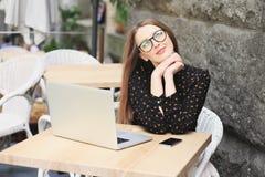 Kobiety są ubranym szkła i czarną koszula w kawiarni Zdjęcia Stock