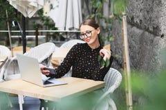 Kobiety są ubranym szkła i czarną koszula w kawiarni Zdjęcie Stock
