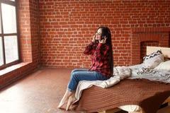 Kobiety słuchająca bezprzewodowa muzyka z hełmofonami od mądrze telefonu w domu Fotografia Royalty Free