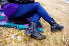 Kobiety ` s cieki w niebieskich dżinsach i czarnych zima butach są na San Fotografia Royalty Free