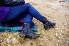 Kobiety ` s cieki w niebieskich dżinsach i czarnych zima butach są na San Zdjęcie Stock