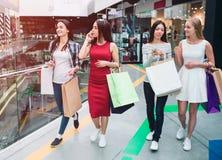 Kobiety ` s firma jest w centrum handlowym Rozszczepiają na dwa grupach Dziewczyna w czerwieni sukni opowiada na telefonie podcza obrazy stock