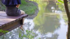 Kobiety ` s iść na piechotę obwieszenie nad krawędzią drewniany jetty zbiory