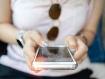 Kobiety ` s ręka używać smartphone obrazy royalty free
