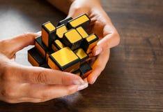 Kobiety ` s ręk chwyta lustra magiczny sześcian na drewnianym tle Fotografia Stock