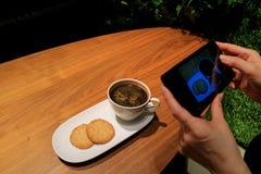 Kobiety ` s ręka Bierze obrazek kawa i ciastka z telefonem komórkowym w sklep z kawą Fotografia Royalty Free