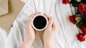 Kobiety ` s ręka, filiżanka czarna kawa i bukiet czerwone róże, koperta z gratulacjami Zdjęcia Royalty Free