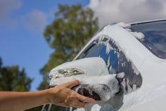 Kobiety ` s ręka myje białego samochodowego ` s strony lustro w Finlandia Zdjęcia Stock