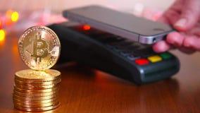 Kobiety ` s ręka płaci bank kartą używać terminal dla zapłaty na tle złociste monety bitcoins _ zdjęcie wideo