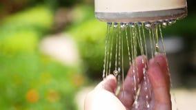 Kobiety ` s ręka pod basen prysznic Ręka zaświecająca jaskrawym światłem słonecznym na zamazanym bokeh zaświeca przeciw tropikaln zbiory wideo