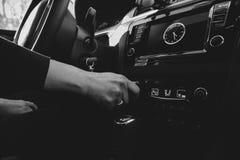 Kobiety ` s ręka przystosowywa upału ogrzewanie siedzenie w samochodzie obrazy stock