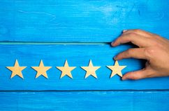 Kobiety ` s ręka stawia kwinty gwiazdę Ilość status jest pięć gwiazdami obrazy stock
