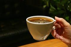 Kobiety ` s ręka Trzyma filiżankę Gorąca kawa w pokoju z Ciepłym oświetleniem Obrazy Stock
