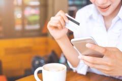 Kobiety ` s ręka trzyma kredytową kartę i uses używają telefon komórkowego Obraz Stock