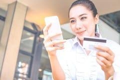 Kobiety ` s ręka trzyma kredytową kartę i uses używają telefon komórkowego Zdjęcie Royalty Free