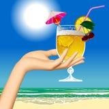 Kobiety ` s ręka trzyma owocowego koktajl przeciw dennej plaży Fotografia Stock