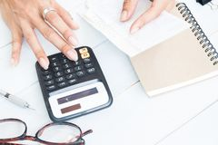 Kobiety ` s ręka używać kalkulatora i trzymający ślizgania, finanse i autobus, Obrazy Stock