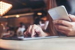 Kobiety ` s ręka wskazuje pastylka komputer osobistego i dotyka podczas gdy używać telefon komórkowego w kawiarni zdjęcia stock