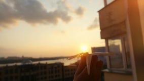 Kobiety ` s ręka z papieru samolotem podczas zmierzchu z słońce racą w slowmotion w dzieciństwie na miasta tle, jak obiektyw zdjęcie wideo