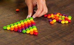 Kobiety ` s ręka zbiera nawet rząd kolorowi cukierki na drewnianym obrazy royalty free