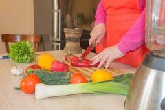 Kobiety ` s ręki ciie pieprzu, za świeżymi warzywami Kobieta kucharz przy kuchnią Szef kuchni ciie warzywa w posiłek fotografia stock