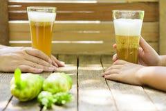 Kobiety ` s ręki mienia noni dziecka i soku ` s wręcza mienia noni sok z noni owoc na drewnianym stole Obraz Royalty Free