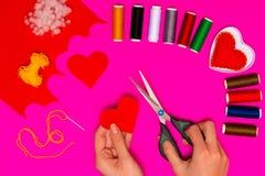Kobiety ` s ręki szą poduszkę w postaci serca na różowią stół Walentynki tło z handmade uszytymi poduszek sercami w kobiecie Obraz Royalty Free