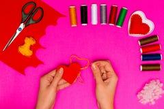 Kobiety ` s ręki szą poduszkę w postaci serca na różowią stół Walentynki tło z handmade uszytymi poduszek sercami w kobiecie Zdjęcia Royalty Free