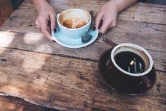 Kobiety ` s ręki trzyma błękitną filiżankę gorąca latte kawa z latte sztuką na drewnianym rocznika stole i pokazuje Obraz Royalty Free