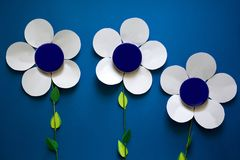 Kobiety ` s ręki trzyma papierowych kwiaty z kruszcowym kremowym słoju zbiornikiem na błękitnego papieru tle Zdjęcie Stock