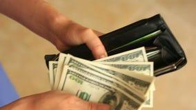 Kobiety ` s ręki trzymają pieniądze klamerkę z dolarami zdjęcie wideo