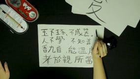 Kobiety ` s ręki writing chińczyka kaligrafia Żeńska ręka trzyma writing muśnięcia Chińskich charaktery obraz royalty free