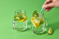 Kobiety ` s ręki wszywek plastikowa słoma w szklanego słój z lemoniadą od naturalnych składników - woda, mennica, plasterki obrazy stock