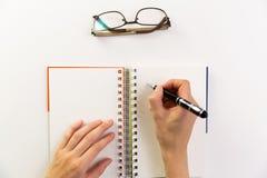 Kobiety ` s ręki z pióra writing na notatniku Nowożytny biurowy biurko zdjęcia royalty free