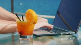Kobiety ` s wręcza pisać na maszynie na laptop klawiaturze Laptopów stojaki na stole przegapia morze, zamykają koktajl zbiory wideo