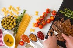 Kobiety ` s wręcza cięcie wołowiny antrykot na czerń kamienia desce smaczny obiad Fotografia Stock