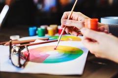 Kobiety ` s wręcza farbę, ołówki i rysunki na stole mienia, Obrazy Stock