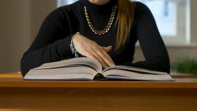 Kobiety ` s wręcza leafing przez książki Kobiety obsiadanie przy stołem leafing przez książki zdjęcia stock