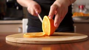 Kobiety ` s wręcza tnącej świeżej pomarańcze na kuchni zbiory wideo