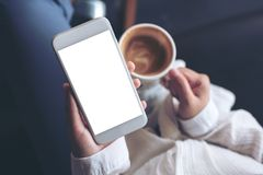 Kobiety ` s wręcza trzymać białego telefon komórkowego z pustym ekranem podczas gdy pijący kawę w kawiarni zdjęcie royalty free